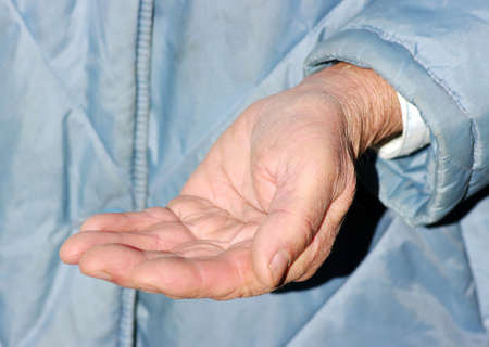 hands of a beggar with coins photo