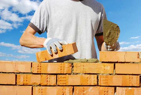 brick work: bricklayer laying bricks to make a wall