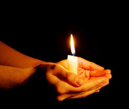 Combusti?n de la vela en una mano en la oscuridad Foto de archivo