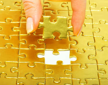 woman fingers holdings gold puzzle Stock Photo - 17493657