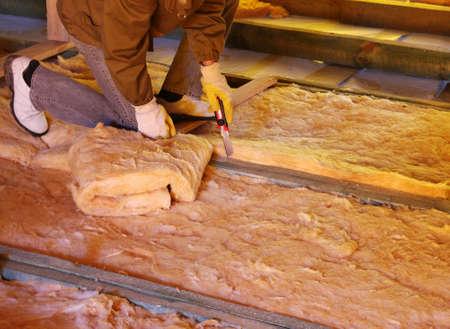 Travailleur de la construction d'isolation thermique grenier de la maison avec de la laine de verre