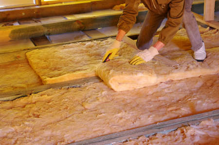 Construction worker thermally insulating house attic with glass wool  Stock Photo