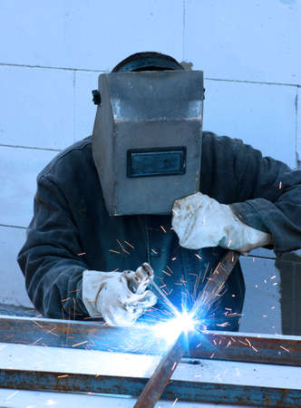 welding worker: welder worker welding metal. Bright electric arc and sparks