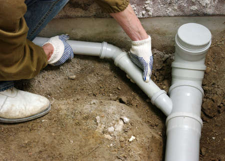 Plumber assembling pvc sewage pipes  photo