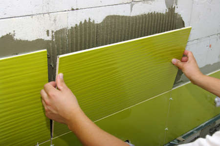 Man installs ceramic tile  Standard-Bild