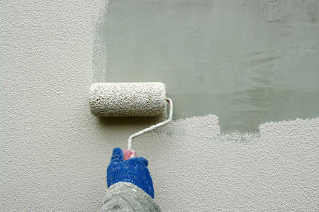 wall painting: Hand painting a white wall with a paint roller Stock Photo