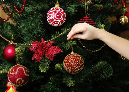 girl hanging decorative toy ball on Christmas tree branch photo