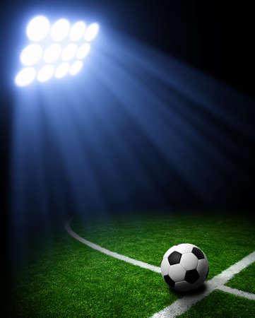 spotlight: Soccer ball on green stadium, arena in night illuminated bright spotlights