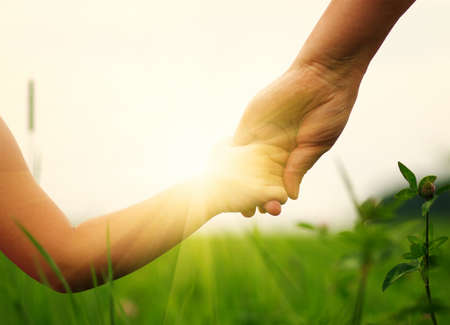 aide à la personne: Mains de la mère et la fille se tenant sur le champ