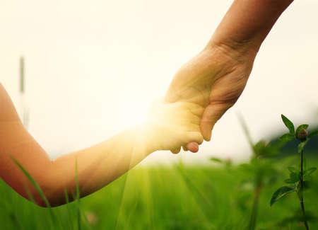 manos: Manos de la madre y la hija que se detienen en el campo