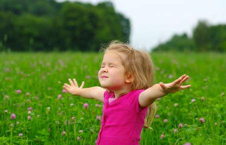 Nettes kleines Mädchen auf der Wiese in Frühlingstag. Kind läuft auf dem Feld. Kind mit ausgestreckten Armen. Freiheit Konzept.
