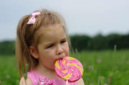 cute little girl eating a lollipop on the field Reklamní fotografie