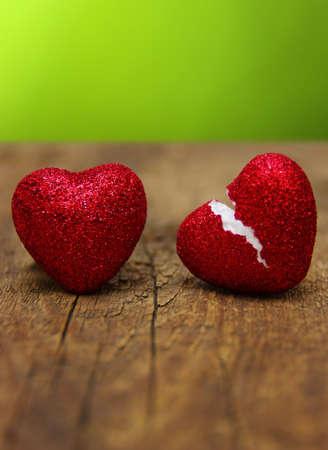 milostný koncept. Zlomené srdce podvádění na dřevo a zelené pozadí. Reklamní fotografie