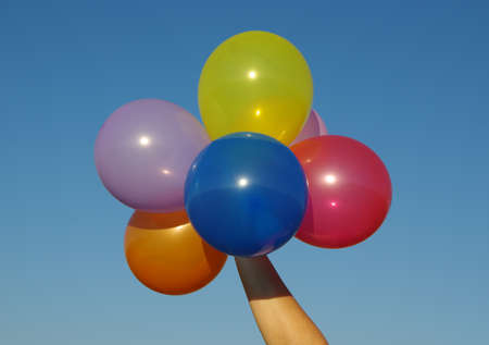 hand holding colorful balloons on sky