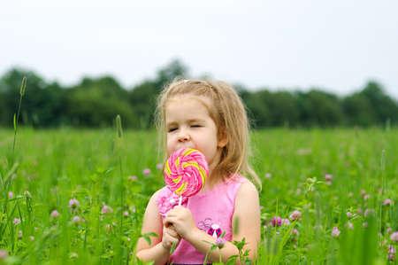 cute little girl eating a lollipop on the field  写真素材