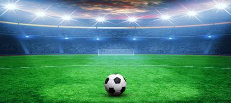Soccer ball on green stadium, arena in night illuminated bright spotlights