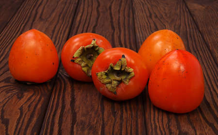 Persimmon fruit on wooden background Stock Photo
