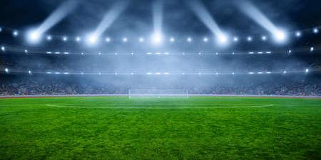 Estadio de fútbol con iluminación, pasto verde y cielo borroso de noche