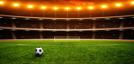 Balón de fútbol en estadio verde, arena en la noche iluminada focos brillantes