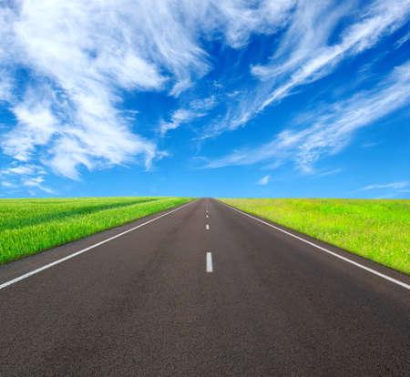 Carretera de asfalto y nubes en el cielo azul en día de verano Foto de archivo