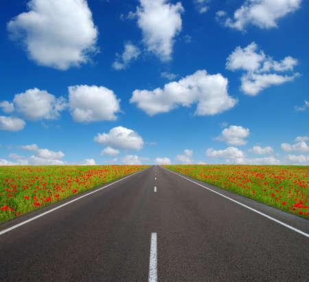 Asphalt car road and clouds on blue sky in summer day Foto de archivo