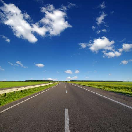 Asphalt car road and clouds on blue sky in summer day Reklamní fotografie