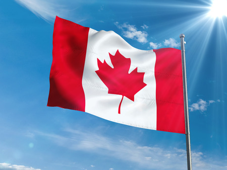 Canadian flag waving in blue sky with sun Stock Photo