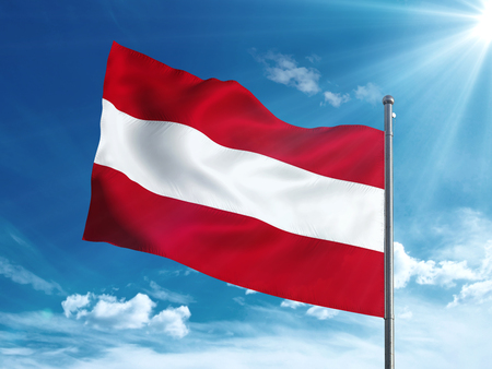 オーストリアの国旗は青い空で手を振っています。 写真素材