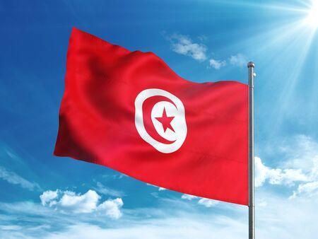 Tunisia flag waving in the blue sky Stock Photo
