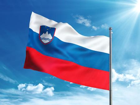 青い空に手を振っているスロベニア フラグ 写真素材
