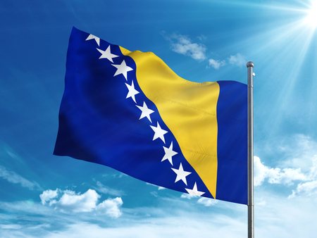 Bosnia and Herzegovina flag waving in the blue sky Stock Photo
