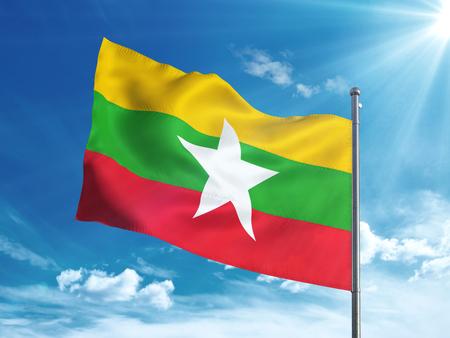 ミャンマーの国旗は青い空で手を振っています。