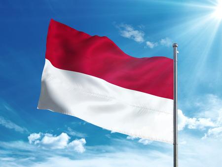 インドネシアの国旗は青い空で手を振っています。 写真素材