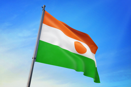 Niger flag waving against blue sky