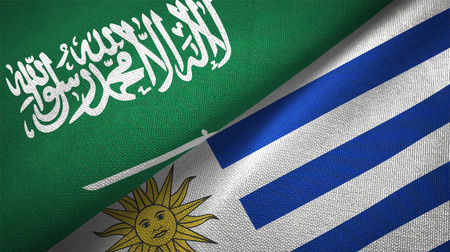 Saudi Arabia and Uruguay flags. Text on saudi arabian flag means - There is no god but God, Muhammad is the Messenger of God Foto de archivo