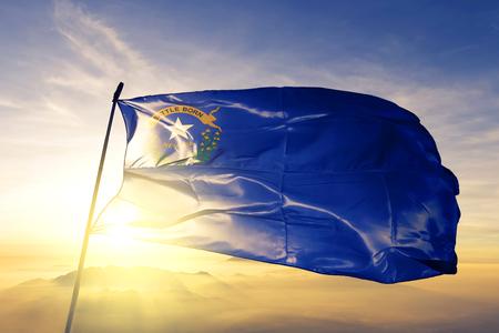 Nevada state of United States flag textile cloth fabric waving on the top sunrise mist fog