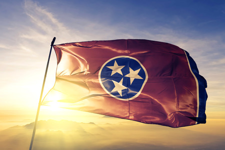 Tennessee state of United States flag textile cloth fabric waving on the top sunrise mist fog