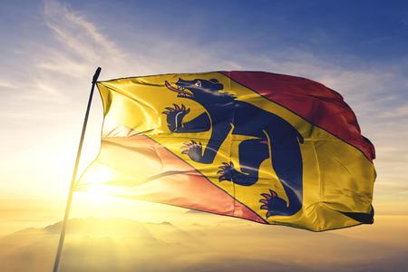 Canton de Berne drapeau tissu textile tissu ondulant sur le dessus du brouillard brouillard lever du soleil