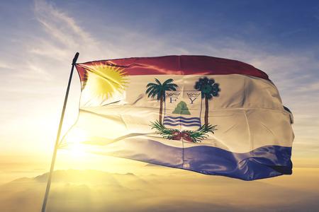Puerto Plata province of Dominican Republic flag textile cloth fabric waving on the top sunrise mist fog