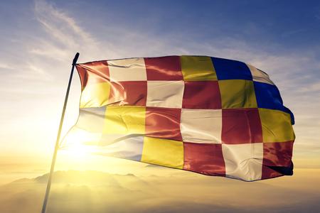 Antwerp province of Belgium flag textile cloth fabric waving on the top sunrise mist fog