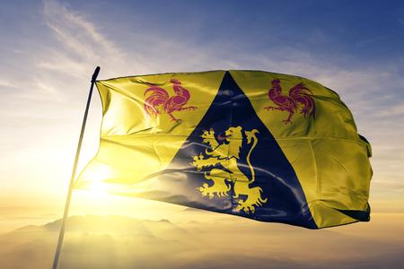 Walloon Brabant province of Belgium flag textile cloth fabric waving on the top sunrise mist fog