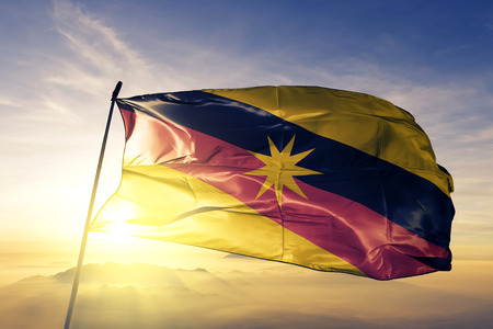 Sarawak state of Malaysia flag textile cloth fabric waving on the top sunrise mist fog Foto de archivo
