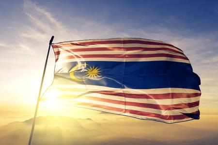 Federal Territory of Kuala Lumpur state of Malaysia flag textile cloth fabric waving on the top sunrise mist fog Stock Photo