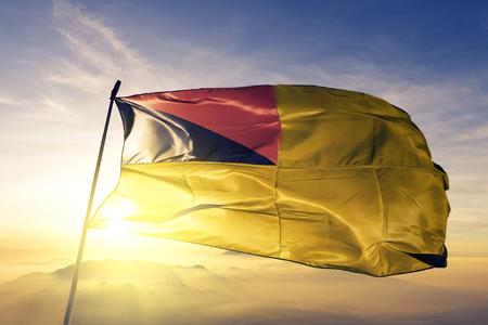Negeri Sembilan state of Malaysia flag textile cloth fabric waving on the top sunrise mist fog