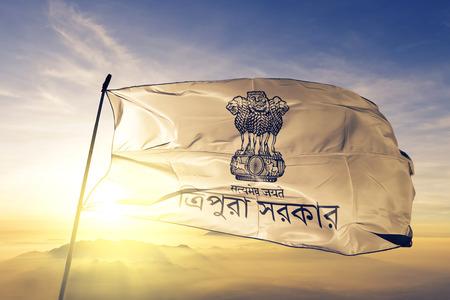 Tripura state of India flag textile cloth fabric waving on the top sunrise mist fog Фото со стока