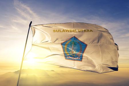 North Sulawesi province of Indonesia flag textile cloth fabric waving on the top sunrise mist fog
