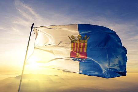 Alicante province of Spain flag textile cloth fabric waving on the top sunrise mist fog Imagens