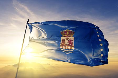 Ourense province of Spain flag textile cloth fabric waving on the top sunrise mist fog Imagens