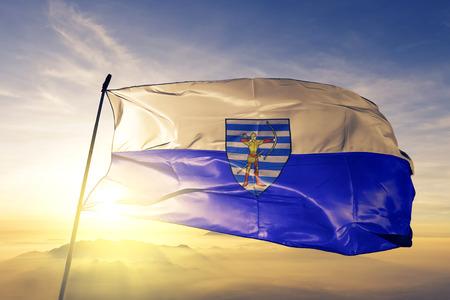 Balti city of Moldova flag textile cloth fabric waving on the top sunrise mist fog