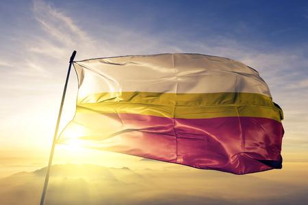 Lesser Poland voivodeship province of Poland flag textile cloth fabric waving on the top sunrise mist fog
